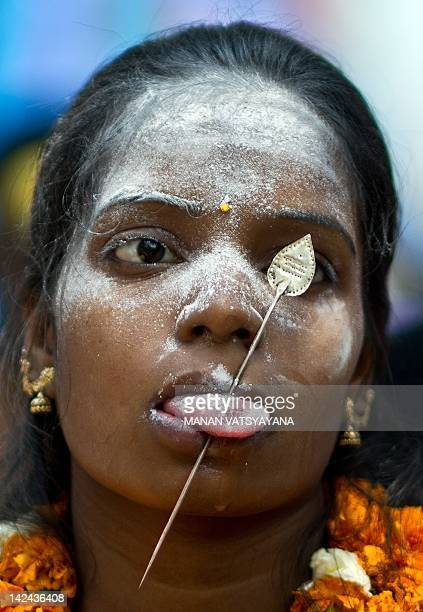 An Indian Tamil Hindu devotee with a steel rod pierced through her tongue takes part in a religious procession for Lord Murugan in New Delhi on April...
