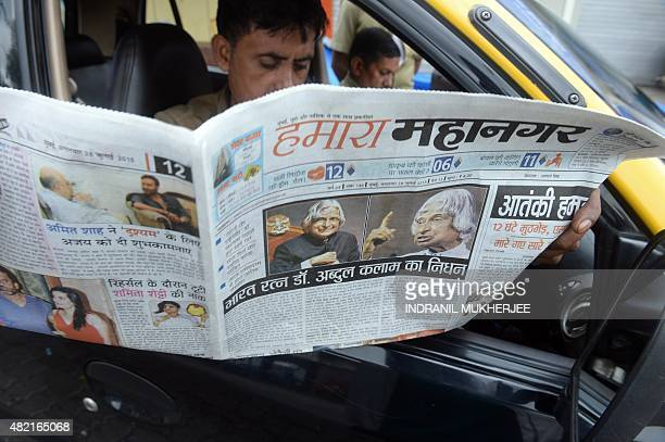 An Indian taxi driver reads a newspaper with the news of the demise of India's former president and top scientist A P J Kalam at the age of 83 on its...