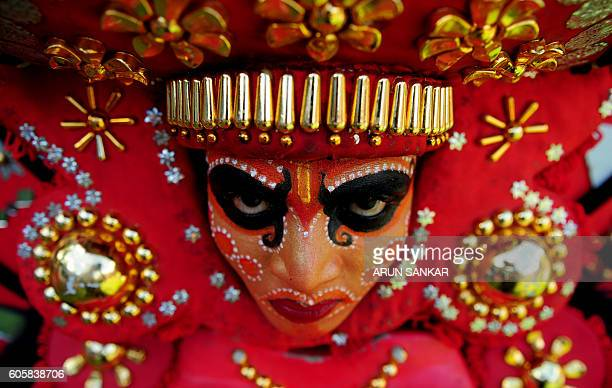 TOPSHOT An Indian 'Theyyam' artist with his face painted waits to perform during the 'Kummati Kali' as part of the annual Onam festival celebrations...