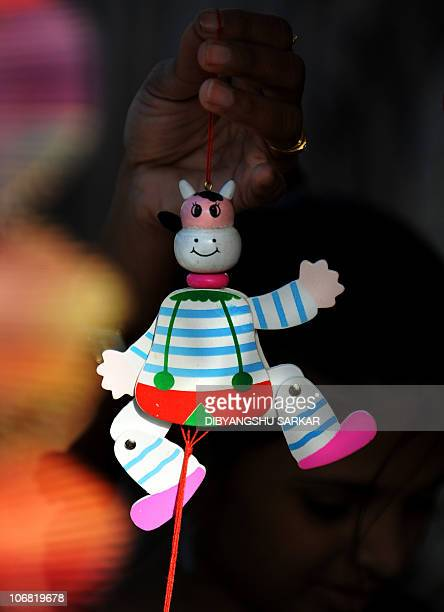 An Indian tourist checks a Channapatna toy at a showroom in Bangalore on November 12 2010 Channapatna toys are a particular form of wooden toys that...