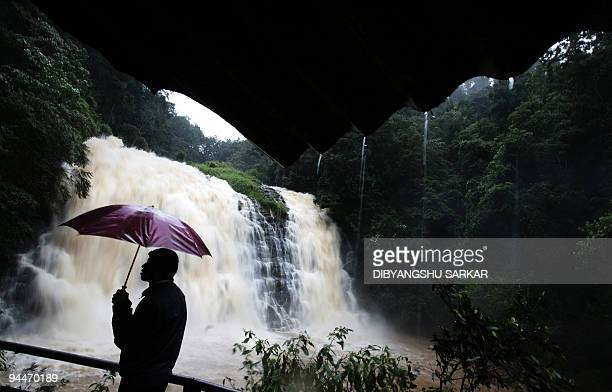 An Indian tourist enjoys the overflowing view of Abbey Falls in Madikery some 320 kms west of Bangalore on August 9 2008 A monsoon is a seasonal...