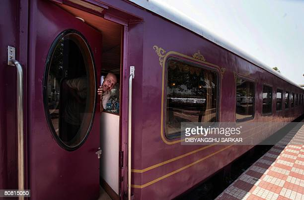 An Indian tourist gestures as he opens the door of a carriage of The Golden Chariot train on the outskirts of Bangalore on April 14 2008 The Golden...