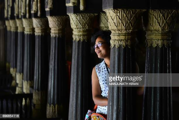 An Indian tourist gets her picture taken next to pillars at Tipu Sultan's Summer Palace in Bangalore on June 17 2017 The palace a popular tourist...