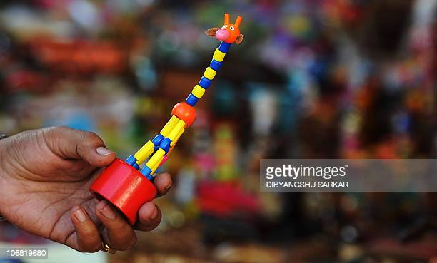 An Indian tourist looks at a Channapatna toy at a showroom in Bangalore on November 12 2010 Channapatna toys are a particular form of wooden toys...