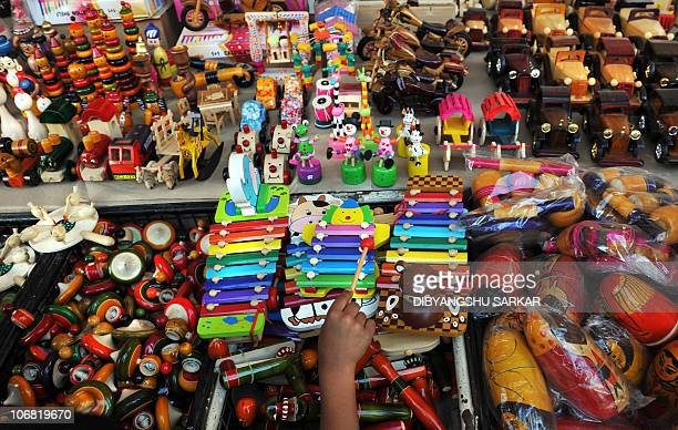 An Indian tourist looks Channapatna toys at a showroom in Bangalore on November 12 2010 Channapatna toys are a particular form of wooden toys that...