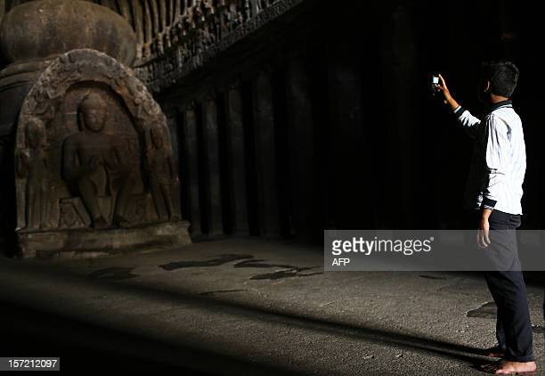 An Indian tourist takes a picture of a Buddhist carving at The Ellora Caves in the western Indian state of Maharashtra on November 16 2012 The 34...