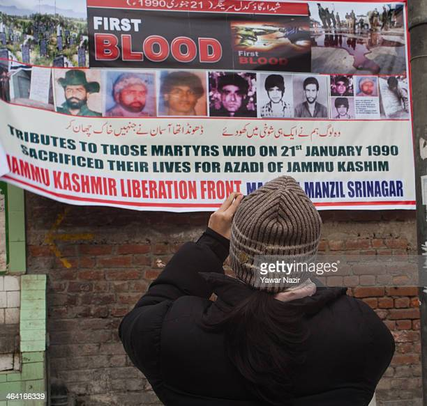 An Indian tourist takes picture of a banner during a protest on the 24th anniversary of the 'Gaw Kadal' massacre on January 21 2014 in Srinagar the...