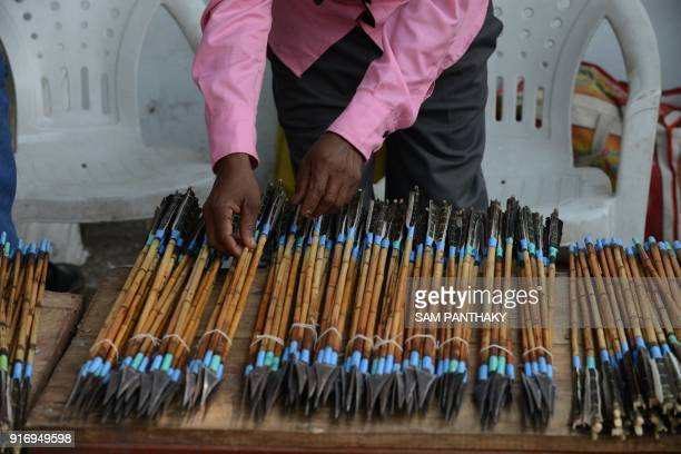 An Indian trader from Chota Udepur a tribal dominated region of Gujarat arranges bows and arrows for sale outside the venue of a mass wedding for...