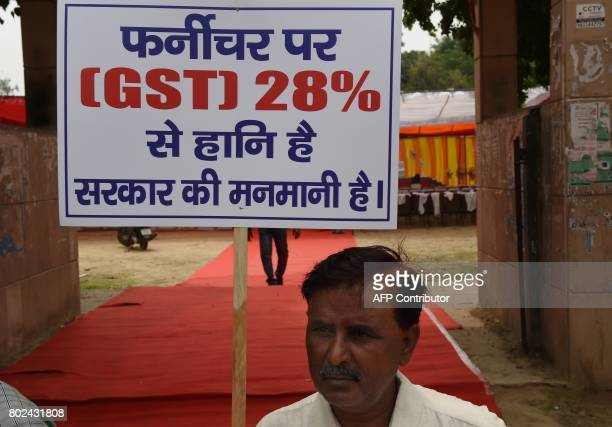 An Indian trader holds a placard during a protest against the forthcoming Goods and Services Tax rates in New Delhi on June 28 2017 India is bracing...