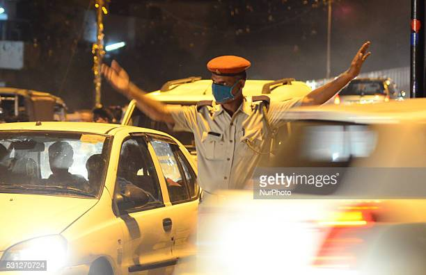 An indian traffic police official wears an anti pollution mask as he controls the traffic on a busy crossing in Allahabad on May 132016According to...