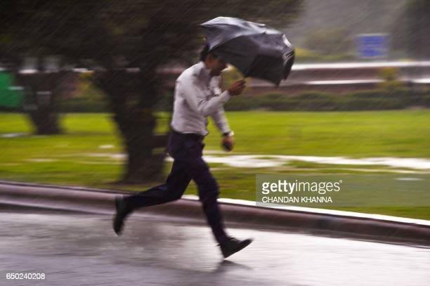 An Indian traffic police personnel runs with his umbrella during a rainfall in New Delhi on March 9 2017 / AFP PHOTO / CHANDAN KHANNA