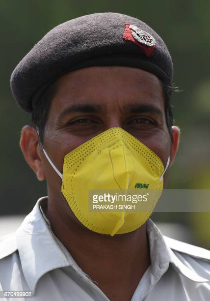 An Indian traffic policeman wears a mask at a traffic red light in New Delhi on April 20 2017 / AFP PHOTO / Prakash SINGH