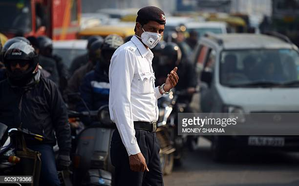An Indian traffic policeman with his face covered by a protective mask handles traffic at an intersection in New Delhi on December 31 2015 Millions...