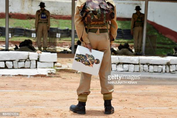 An Indian trainee recruit holds his target board after a shooting practice session at the firing range of Parachute Regiment Training Centre in...