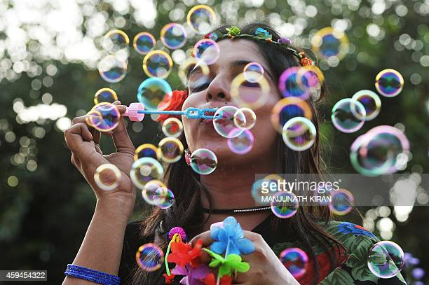 An Indian transgender activist blows bubbles during the annual Bengaluru Pride March in Bangalore on November 23 2014 The annual march is aimed at...