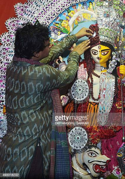 An Indian transgender devotee performs a ritual in front of a transgender statue of the Hindu goddess Durga at a pandal during the Durga Puja...