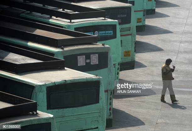 An Indian transport employee checks his mobile phone next to buses parked at a depot during a transport strike in Chennai on January 5 2018 The Tamil...