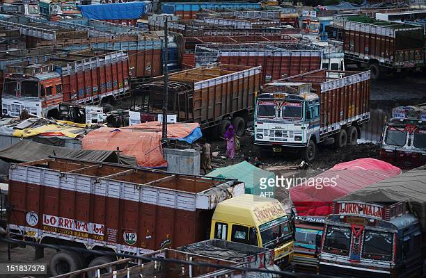 An Indian trash collector looks for rubbish between parked trucks at the Sanjay Gandhi Transport Nagar a transport rest area in New Delhi early on...