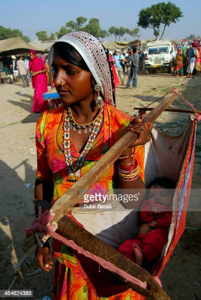 CONTENT] An Indian tribal mother carrying her baby while watching Pushkar Camel festival in Pushkar Rajasthan India on November 122008Thousands of...