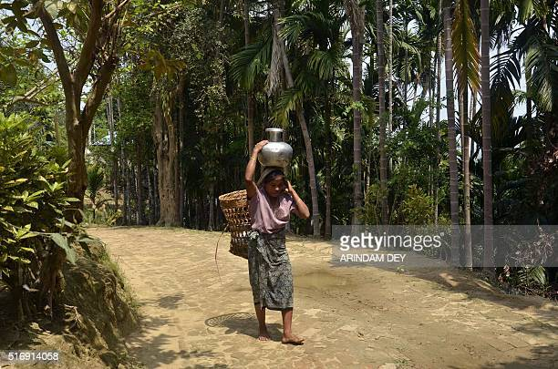 An Indian tribal woman carries water from a rivulet in a jug on her head for drinking during World Water Day in Baramura Hills on the outskirts of...