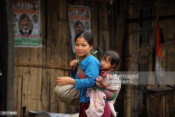 An Indian tribal woman carrying a child walks past a poster of Congress party State Assembly candidate Kipa Babu in Itanagar capital of Arunachal...
