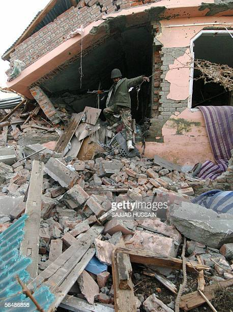An indian trooper leaves one of the two houses which were reduced to rubble during a firefight between Islamic rebels and Indian security forces at...
