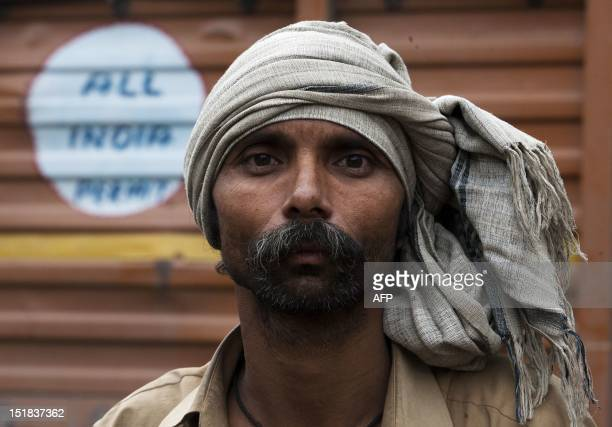 An Indian trucker poses for a photo at Sanjay Gandhi Transport Nagar a transport rest area in New Delhi on September 8 2012 Truckers spend as much as...