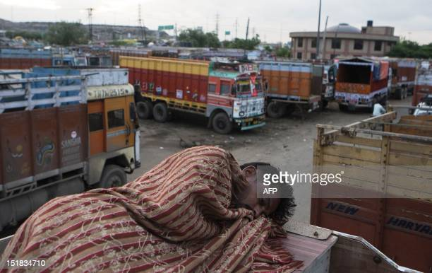 An Indian trucker rests on the roof his truck at Sanjay Gandhi Transport Nagar a transport rest area in New Delhi early on September 8 2012 At the...