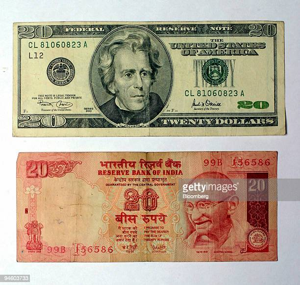 An Indian twenty rupee note below is photographed along with a US twenty dollar bill above in New Delhi India on Sunday September 3 2006 India's...