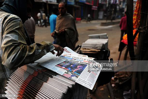 An Indian vendor arranges newspapers carrying reports of the newly elected US President Donald Trump on a street in Allahabad on November 10 2016...
