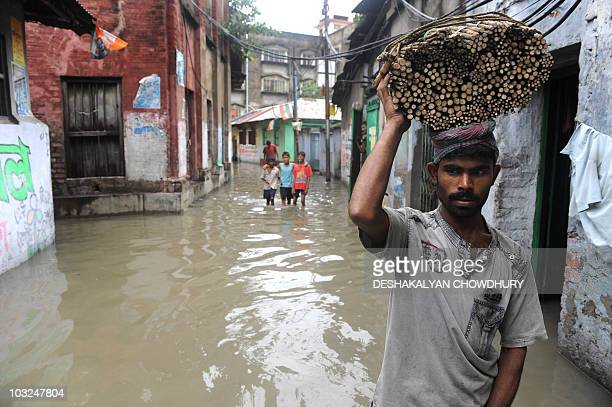 An Indian vendor carries a basket of neem tree branches which are used as toothbrushes as he walks in a water logged street of Kolkata on July 31...