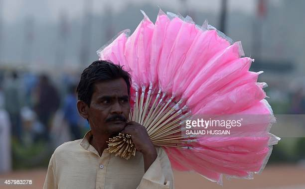 An Indian vendor carries cotton candy for sale at India Gate in New Delhi on October 28 2014 India is part of a global trend that is advancing...