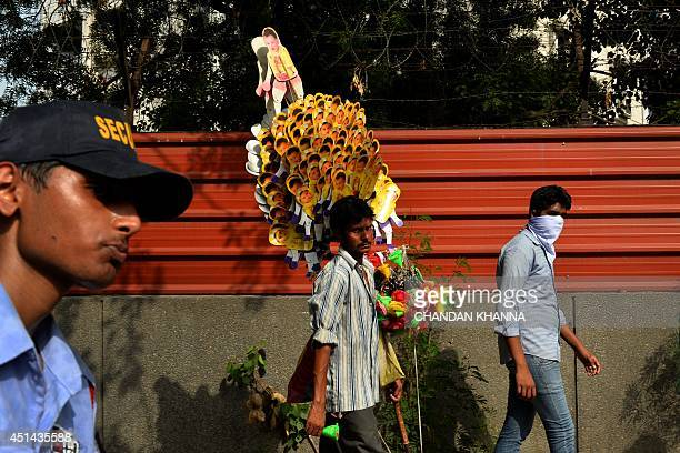 An Indian vendor carries toys for sale during the annual Rath Yatra or chariot procession in New Delhi on June 29 2014 The annual Hindu procession...