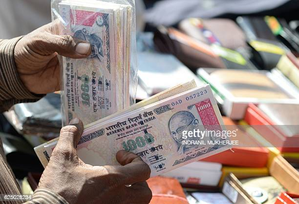 An Indian vendor displays wallets made from replica prints of the demonetised 500 and 1000 INR currency notes prints for sale at a stall in Mumbai on...