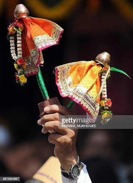 An Indian vendor holds up miniature 'Gudis' for sale during a procession celebrating 'Gudi Padwa' or the Maharashtrian new year in Mumbai on March 31...