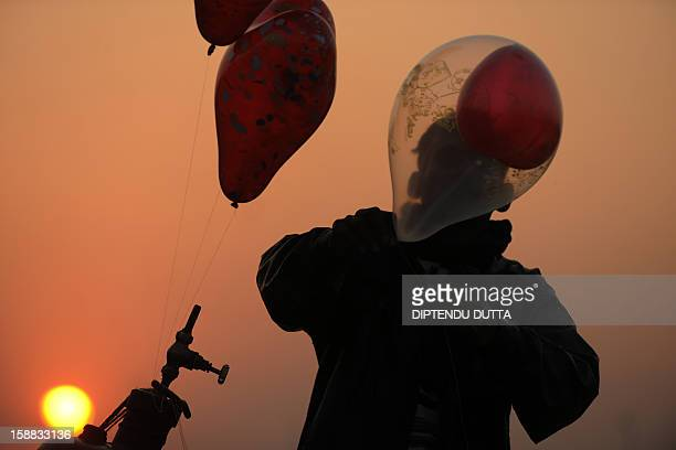 An Indian vendor inflates balloons as the sunsets in Siliguri on December 31 2012 Sydney will kick off a wave of dazzling firework displays welcoming...