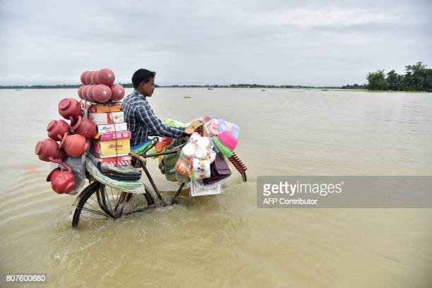 TOPSHOT An Indian vendor pushes a bicycle carrying his wares through floodwaters in Balimukh Ashigarh village in Morigoan district in India's...