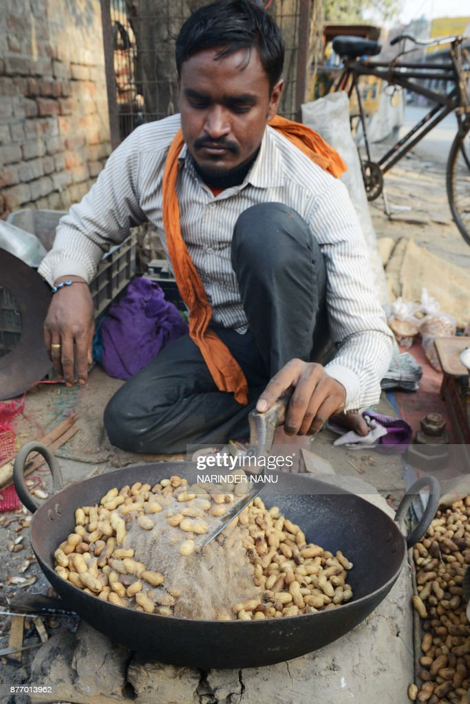 An Indian vendor roasts peanuts at a roadside stall in Amritsar on November 21 2017 / AFP PHOTO / NARINDER NANU