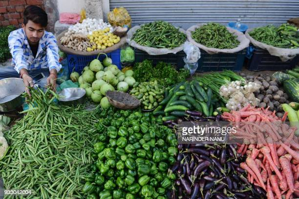 An Indian vendor sell vegetables at a roadside stall in Amritsar on March 17 2018 / AFP PHOTO / NARINDER NANU