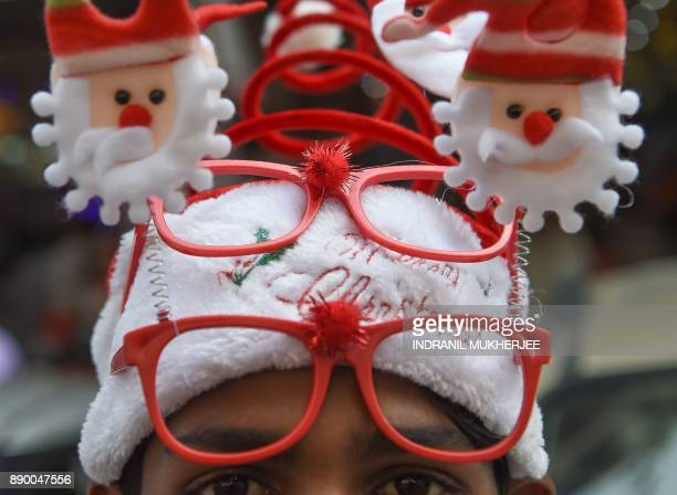 An Indian vendor sells decorative Christmas headwear at an outdoor market in Mumbai on December 11 2017 / AFP PHOTO / INDRANIL MUKHERJEE