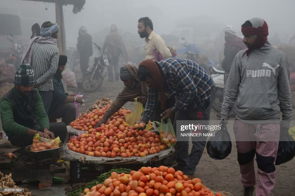 An Indian vendor sells tomatoes at a wholesale vegetable market on the outskirts of Amritsar on January 3 2018 / AFP PHOTO / NARINDER NANU