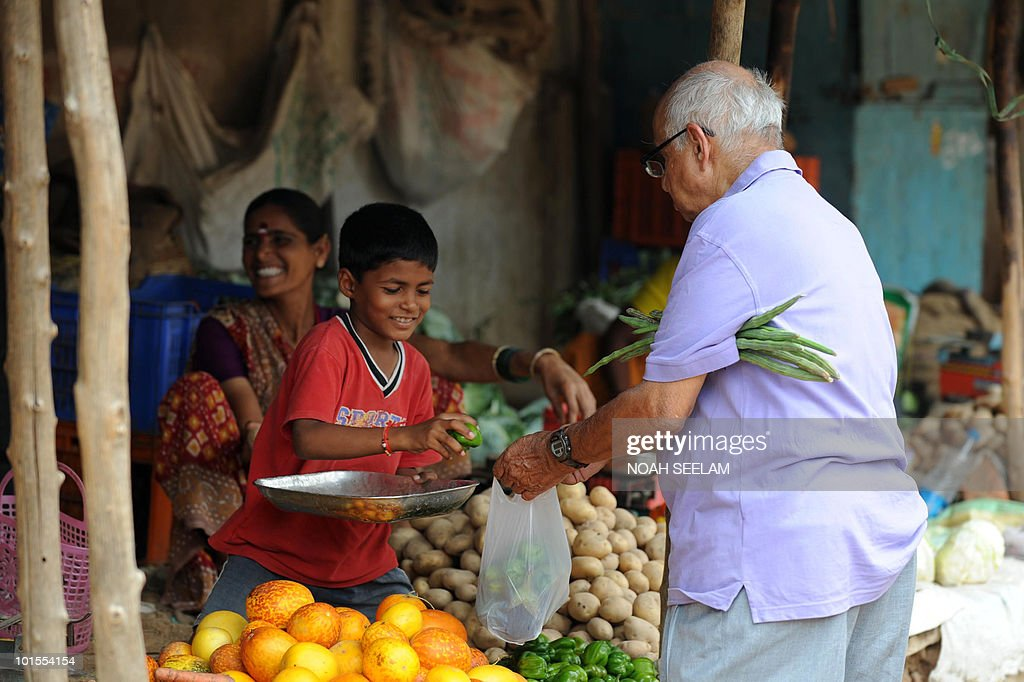 An Indian vendor sells vegetables to a customer at a vegetable market in Hyderabad on June 2, 2010. The meteorological department has forecasted a normal monsoon this year which will help boost the agricultural output and bring down the rising food inflation. AFP PHOTO/Noah SEELAM