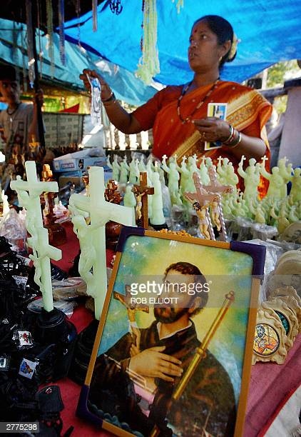 An Indian vendor sets up her display of portraits and statues of Saint Francis Xavier outside the grounds of the Basilica of Bom Jesus at the Saint...