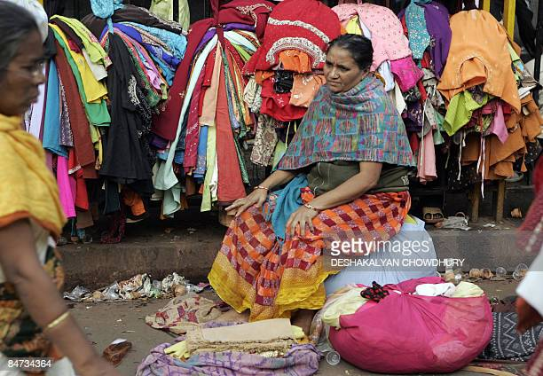 An Indian vendor sits amongst her wares as bargain hunters browse through clothing at a second hand clothing market in Kolkata on February 11 2009...