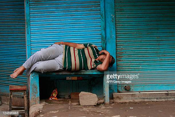 An Indian vendor sleeps in front of closed shops in New Delhi on September 11 2011 India's economy will grow at a slower pace in the JulySeptember...