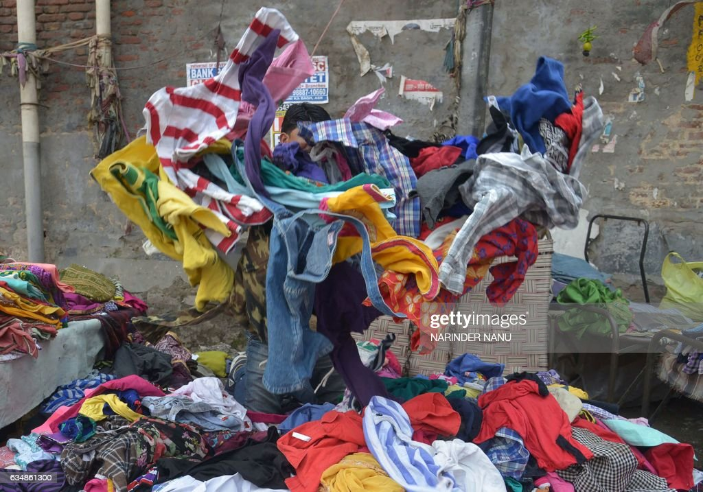 TOPSHOT An Indian vendor sorts through used summer clothes at a roadside stall in Amritsar on February 12 2017 / AFP PHOTO / NARINDER NANU