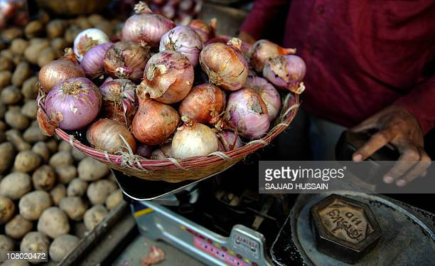 An Indian vendor weighs onions at a vegetable market in Mumbai on September 17, 2009. India reported a return to inflation as a result of soaring...