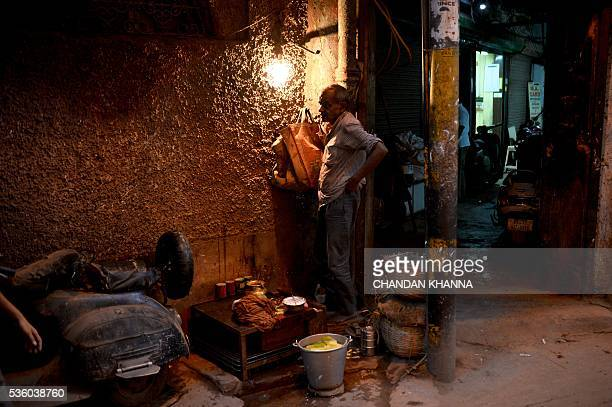 An Indian vendor who sells betelnut mouth freshener waits for customers at his makeshift shop in the old quarters of New Delhi on May 31 2016 / AFP /...