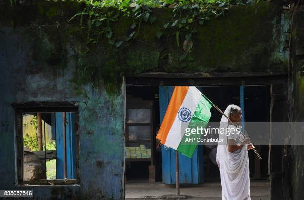 An Indian villager carries the national flag during Independence Day celebrations in Majhdia village of Nadia district east of Krishnanagar in West...