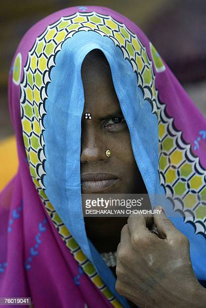 An Indian villager covers her face as she prepares food in a temporary tented shelter on the national highway after being washed out of her home at...